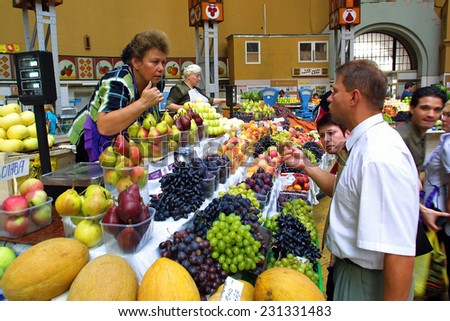 KIEV, UKRAINE, 16 AUGUST 2003:  Shoppers hunt for locally made fruits and vegetables at a covered market in Kiev.  - stock photo