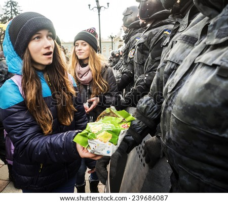 KIEV, UKRAINE - December 23, 2014: Girl cookie Guards treats. -- To break through the cordon of police and four special forces in full uniform, - stock photo