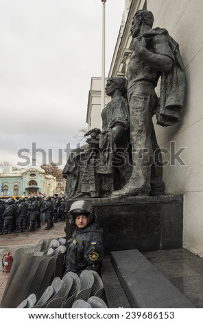 KIEV, UKRAINE - December 23, 2014: Policeman sits under the monument near the entrance to the Verkhovna Rada, beside him stacked shields.  - stock photo