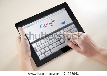 KIEV, UKRAINE - DECEMBER 03, 2011: Woman holding Apple iPad with Google search web page on a screen. This second generation of Apple iPad is designed and development by Apple inc. in march 2011. - stock photo