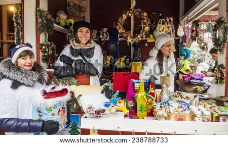 KIEV, UKRAINE - December 19 2014: Young girls are selling Christmas souvenirs -- Christmas market on the square near St. Sophia - stock photo