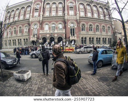 "KIEV, UKRAINE - Feb 25, 2015: A man walks past a rally near the National Bank. -- Activists of the ""credit Maidan"", which Kiev left to fend for themselves - stock photo"