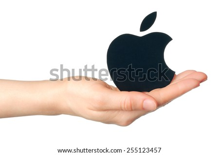 KIEV, UKRAINE - FEBRUARY 16, 2015:Hand holds apple logotype printed on paper on white background.Apple is an American multinational corporation, that sells consumer electronics and personal computers. - stock photo