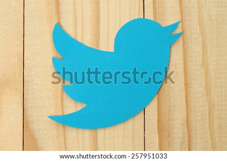 KIEV, UKRAINE - FEBRUARY 19, 2015:Twitter logotype bird printed on paper. Twitter is an online social networking service that enables users to send and read short messages. - stock photo