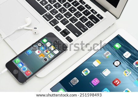 KIEV, UKRAINE - JANUARY 29, 2015: Apple iPhone 5s, iPad Air 2 and MacBook Air. Apple Inc. is an American multinational corporation that designs, develops, and sells consumer electronics. - stock photo