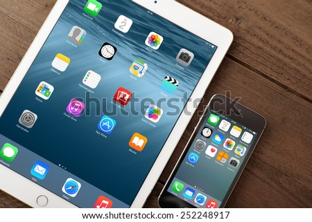 KIEV, UKRAINE - JANUARY 29, 2015: Apple iPhone 5s, iPad Air 2 on table. Apple Inc. is an American multinational corporation that designs, develops, and sells consumer electronics. - stock photo