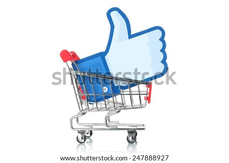 KIEV, UKRAINE - JANUARY 24, 2015: Facebook thumbs up sign printed on paper and placed into shopping cart on white background. Facebook is a well-known social networking service. - stock photo