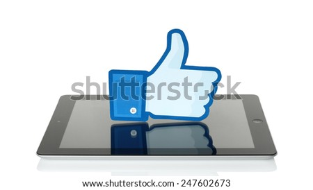 KIEV, UKRAINE - JANUARY 24, 2015: Facebook thumbs up sign printed on paper and placed on iPad on white background. Facebook is a well-known social networking service. - stock photo