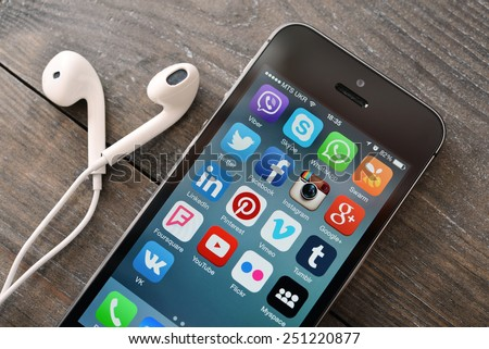 KIEV, UKRAINE - JANUARY 29, 2015: Social media icons on screen of iPhone. Social media are most popular tool for communication, sharing information and content between people in internet network. - stock photo