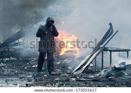 KIEV, UKRAINE - 23 JANUARY 2014: Unknown demonstrator with stick at the Independence square during Ukrainian revolution on January 23, 2014 in Kiev, Ukraine. - stock photo