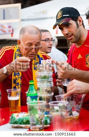 KIEV, UKRAINE - JUL 1: Unidentified Spanish and Ukrainian football fans drink beer before final match EURO 2012 Spain vs. Italy on July 1, 2012 in Kiev, Ukraine - stock photo