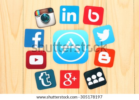 KIEV, UKRAINE - JULY 01, 2015: Around AppStore icon are placed famous social media icons such as: Facebook, Twitter, Blogger, Linkedin and others, printed on paper and placed on wooden background. - stock photo