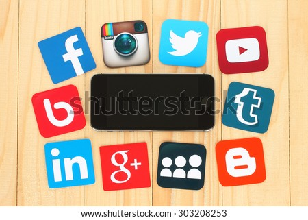 KIEV, UKRAINE - JULY 01, 2015: Famous social media icons such as: Facebook, Twitter, Blogger, Linkedin, Tumblr, Myspace and others, printed on paper and placed around iPhone on wooden background. - stock photo