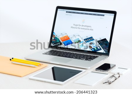 KIEV, UKRAINE - JULY 10, 2014: Studio shot of brand new Apple MacBook Pro presenting new iOS 8 for developers, with Apple mobile devices and office tools on a modern desk. - stock photo
