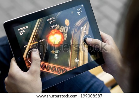 KIEV, UKRAINE - JUNE 05, 2011: Man playing in Death Rally game on brand new Apple iPad. Apple iPad2  was released in March, 2011. Death Rally is popular game, develop by Remedy Entertainment. - stock photo