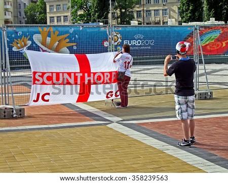 KIEV, UKRAINE - JUNE 15: Sport fans making photo on the street during EURO 2012 on June 15,2012 in Kiev,UKRAINE. EURO 2012 football championship started on June 08 in Ukraine and Poland.  - stock photo