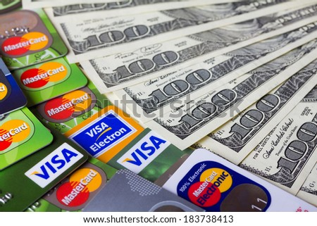 KIEV, UKRAINE - March 22: Pile of credit cards, Visa and MasterCard, credit, debit and electronic with US dollar bills, in Kiev, Ukraine, on March 22, 2014. Selective focus. - stock photo