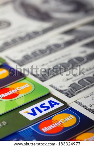 KIEV, UKRAINE - March 22: Pile of credit cards, Visa and MasterCard, with US dollar bills, in Kiev, Ukraine, on March 22, 2014. Shallow DOF. - stock photo