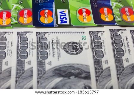 KIEV, UKRAINE - March 22: Pile of credit cards, Visa and MasterCard, with US dollar bills, in Kiev, Ukraine, on March 22, 2014. Selective focus on cards. - stock photo