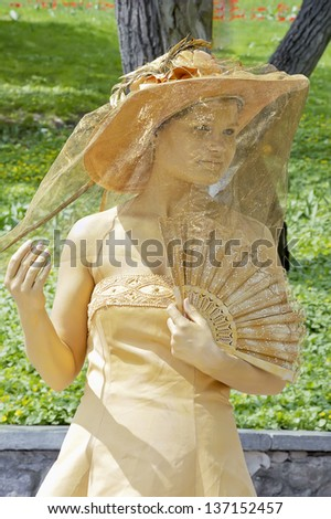 KIEV, UKRAINE - MAY 01: An unidentified busking mime under a veil performs in Spivoche Pole park in Kiev, Ukraine on May 01, 2013. Living golden statue is the entertainment for the tourists. - stock photo