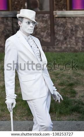 KIEV, UKRAINE - MAY 11: An unidentified busking mime with walking stick performs on Khreshchatyk street in Kiev, Ukraine on May 11, 2013. Living statues are the entertainment for the tourists. - stock photo
