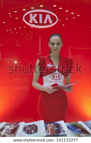 KIEV, UKRAINE - MAY 29: Presenter in red dress work on Korean KIA Motors booth during SIA' 2013 21st Kyiv International Motor Show in International Exhibition Centre on May 29, 2013 in Kiev, Ukraine. - stock photo