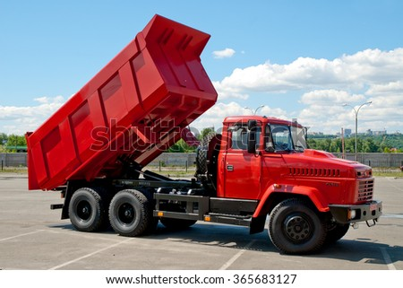 Kiev, Ukraine - May 26,  2009.. Red dump truck with the body lifted for unloading. - stock photo