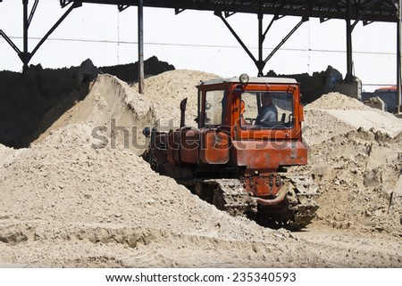 KIEV, UKRAINE - May 17 2013: The territory of the of the concrete plant. Bulldozer is gaining sand - stock photo