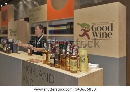 KIEV, UKRAINE - NOVEMBER 21, 2015: Unrecognized presenter works on Good Wine Highland and Speyside Single Malt Scotch Whiskey booth at 1st Ukrainian Whisky Dram Festival in Parkovy Exhibition Center. - stock photo