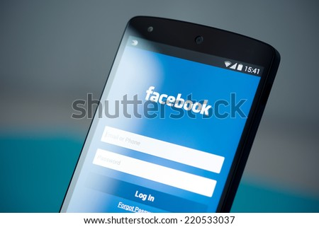 Kiev, Ukraine - September 22, 2014: Close-up photo of brand new Google Nexus 5, powered by Android 4.4 version, with Facebook login account page on a screen.  - stock photo