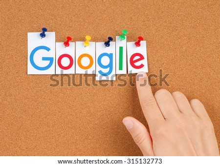 KIEV, UKRAINE - SEPTEMBER 02, 2015:New Google logotype printed on paper, cut and pinned on cork bulletin board with hand.Google is USA multinational corporation. - stock photo