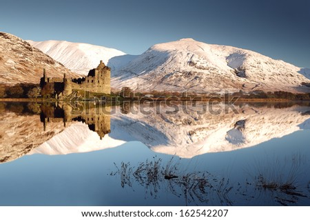 Kilchurn Castle and snow covered mountains reflecting off Loch Awe on a beautiful crisp morning. Dalmally, Scotland. - stock photo