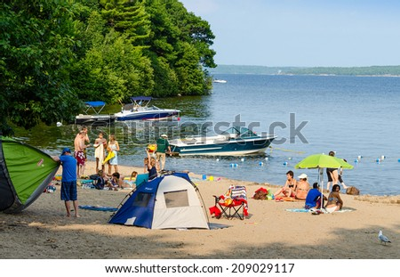 KILLBEAR PROVINCIAL PARK - AUGUST 2, 2014: Vacationing families on one of the sandy beaches at the Killbear Provincial Park in Ontario - stock photo
