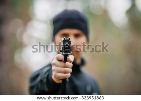 killer with gun isolated on a outdoor background - stock photo