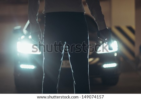 Killer with handgun. Cropped image of men with handgun standing in front of car - stock photo