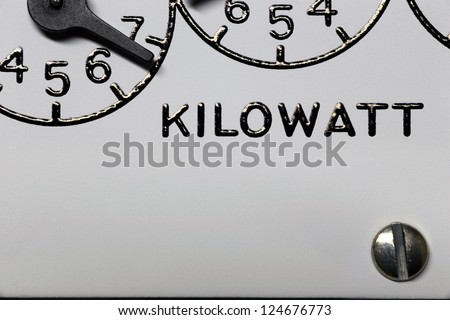 Kilowatt hour electric meter register dial digits and pointers closeup - stock photo