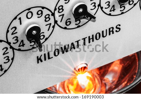Kilowatt hour electric meter register dials with light bulb shining below - stock photo