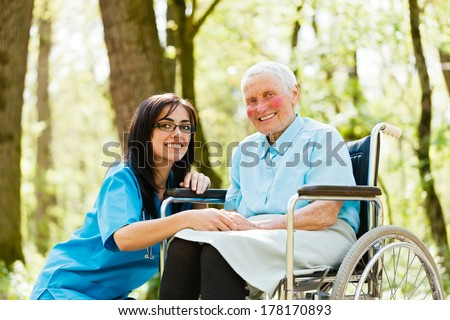 Kind nurse taking care of senior lady patient in wheelchair. - stock photo