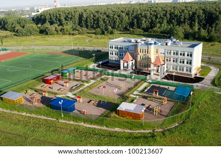 kindergarten building with playing and sports area - stock photo