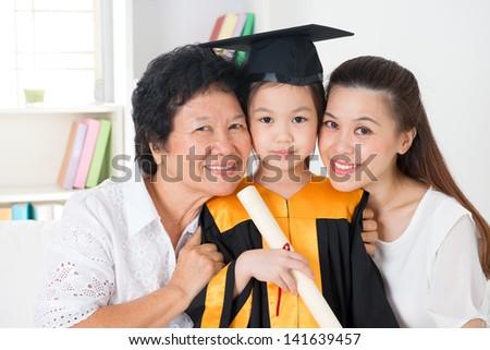 Kindergarten graduation. Happy Asian family, grandparent, parent and grandchild on her kindergarten graduate day. - stock photo