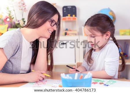 Kindergarten Teacher And Little Girl Drawing Lessons at School - stock photo