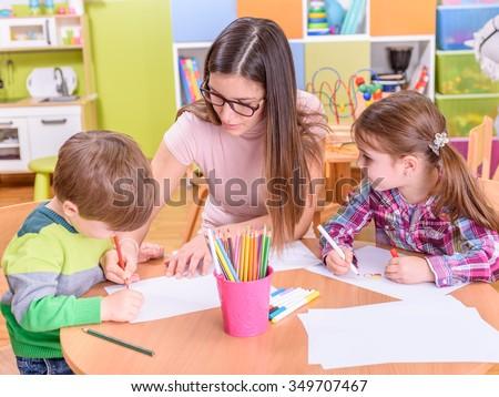 kindergarten teacher helping children on creative art class - stock photo