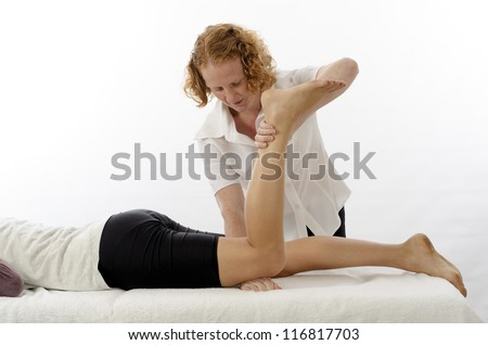 Kinesiologist or physiotherapist treating flexors - stock photo