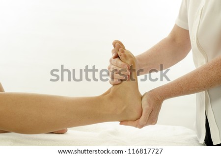 Kinesiologist or physiotherapist treating foot tibialis - stock photo
