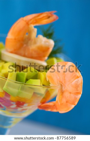 King prawn on the rim of a cocktail glass containing a salad of onion, pepper, mango and avocado, calamari, king prawn and dill (Selective Focus, Focus on the right side of the prawn on the glass rim) - stock photo