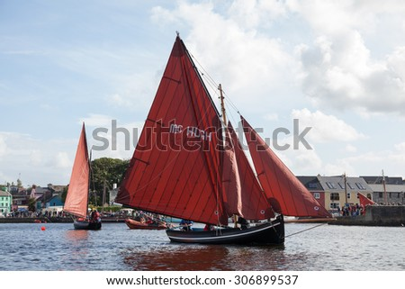 KINVARA, IRELAND - AUGUST 15: Traditional wooden boats Galway Hooker compete in the race during anual Gathering of the Boats festival on August 15, 2015, in Kinvara, Ireland. - stock photo
