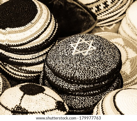 Kippah with Magen David (Star of David) and other Yarmulkes for sale at the market in Jerusalem (Israel). Closeup. Selective focus on the upper corner of the Magen David. Jewish background. Sepia. - stock photo
