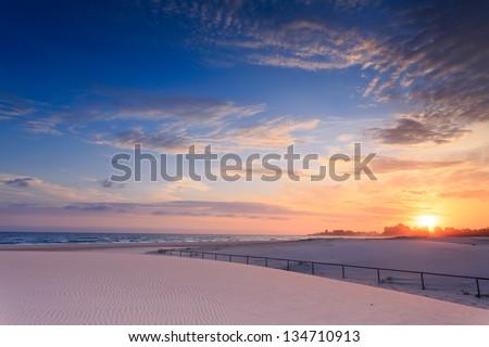 Kirra Beach at sunrise with interesting sand ripples in foreground (Kirra Beach, Queensland, Australia) - stock photo