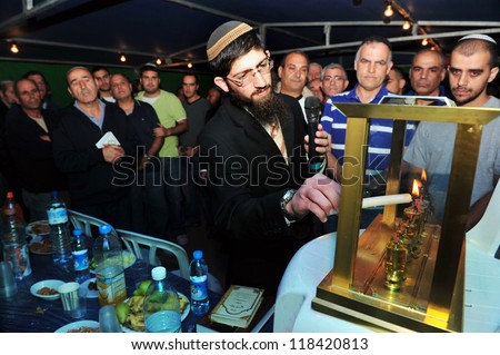 KIRYAT GAT - DECEMBER 07: Family members of Caramel bus disaster victim Roy Bitton light the seventh candle for the Jewish holiday Hanukkah at the mourning tent in Kiryat Gat on December 07 2010. - stock photo
