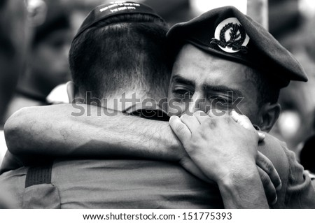 KIRYAT MALACHI, ISR - JULY 07:Israeli soldiers grief for the lost their comrade in arms on  July 7 2006.Israel has suffered over 20,000 troops killed and 75,000 wounded since 1948. - stock photo